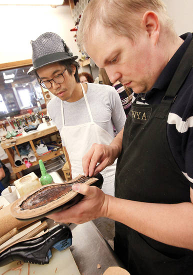Hungarian shoemaker Marcell Mrsán, right, works with student Matt Huang, from Toronto on Thursday during a class at Sorrell Custom Boots in Guthrie.  Photo By David McDaniel,  The Oklahoman