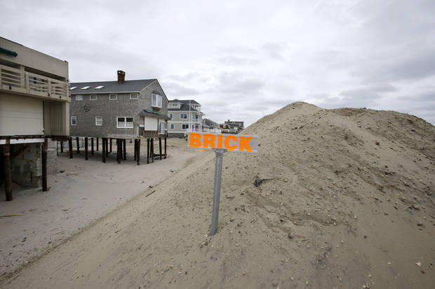 A sign identifies the town Brick on a huge dune piled near the Atlantic Ocean in Brick Township, N.J., Friday, Feb. 22, 2013, to protect homes, many already badly damaged by Superstorm Sandy. (AP Photo/Mel Evans)