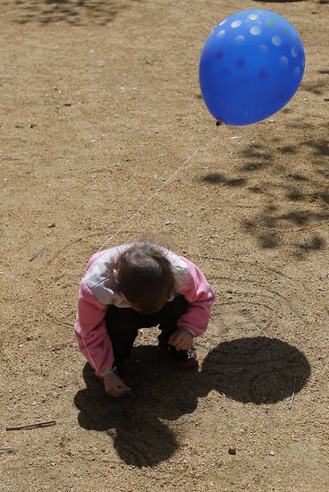Jiana Guo, 3 1/2, daughter of artist Yongqun Guo, draws in the dirt with balloon in tow at the Festival of the Arts in downtown Oklahoma City  Wednesday, April 24, 2013.  Photo by Doug Hoke, The Oklahoman