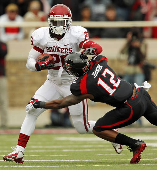 Oklahoma's Damien Williams (26) tries to get past Texas Tech's D.J. Johnson (12) during a college football game between the University of Oklahoma (OU) and Texas Tech University at Jones AT&T Stadium in Lubbock, Texas, Saturday, Oct. 6, 2012. OU won, 41-20. Photo by Nate Billings, The Oklahoman