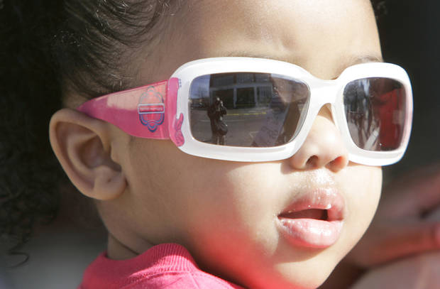 Alana Robison, 2, watches the parade Monday in Oklahoma City. Photos by Steve Gooch,  The Oklahoman