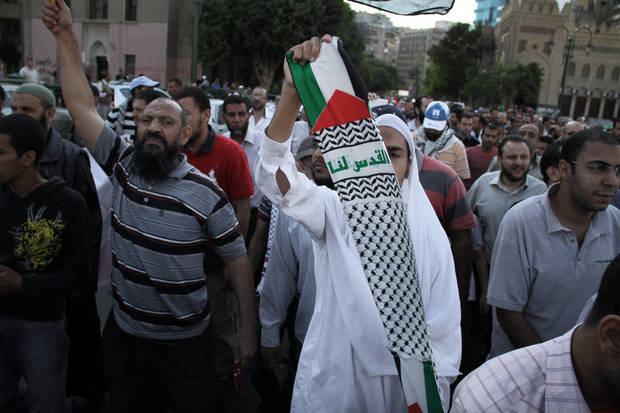 "An Egyptian protester holds a scarf with Arabic that reads ""Jerusalem is ours,"" during a protest in solidarity with Gaza after Israel launched its operation on Wednesday with the assassination of Hamas' top military commander in Cairo, Egypt, Thursday, Nov. 15, 2012. Egypt asked the United States to push Israel to stop its offensive against Hamas militants in the Gaza Strip, warning that the violence could ""escalate out of control,"" the Foreign Ministry said Thursday. (AP Photo/Mohammed Abu Zaid)"