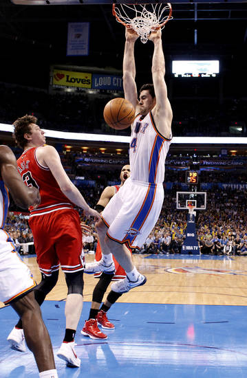 Oklahoma City's Nick Collison (4) dunks over Chicago's Omer Asik (3) during the NBA basketball game between the Chicago Bulls and the Oklahoma City Thunder at Chesapeake Energy Arena in Oklahoma City, Sunday, April 1, 2012. Photo by Sarah Phipps, The Oklahoman