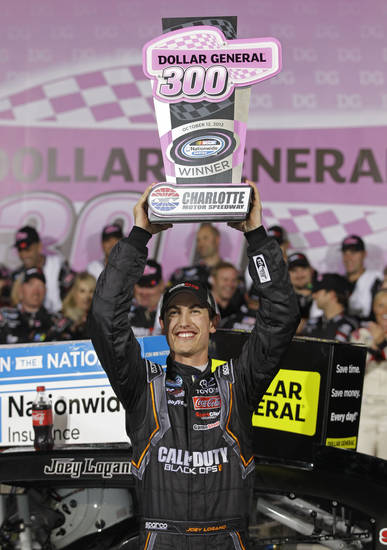 Joey Logano raises the trophy after winning the NASCAR Dollar General 300 Nationwide Series auto race in Concord, N.C., Friday, Oct. 12, 2012. (AP Photo/Chuck Burton)