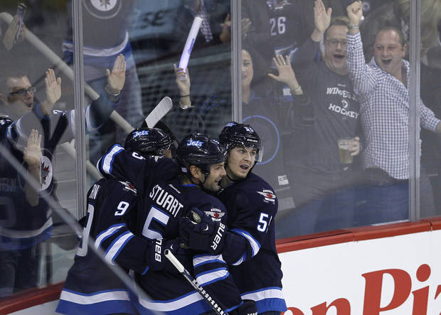 Winnipeg Jets' Evander Kane (9), Mark Stuart (5) and Mark Scheifele (55) celebrate Kane's goal against the Los Angeles Kings during the first period of an NHL hockey game in Winnipeg, Manitoba, on Friday, Oct. 4, 2013. (AP Photo/The Canadian Press, John Woods)