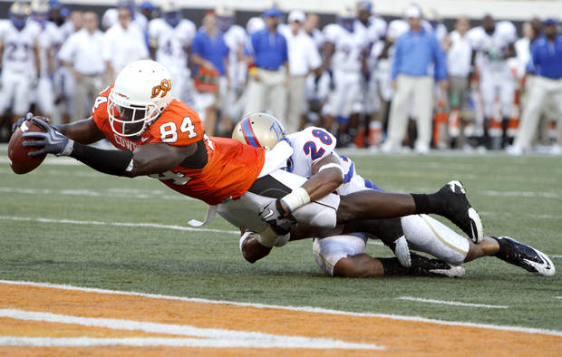 Oklahoma State wide receiver Hubert Anyiam (84) stretches for a touchdown as Tulsa's Lowell Rose (28) tackles him during the college football game between the University of Tulsa (TU) and Oklahoma State University (OSU) at Boone Pickens Stadium in Stillwater, Oklahoma, Saturday, September 18, 2010. Photo by Sarah Phipps, The Oklahoman