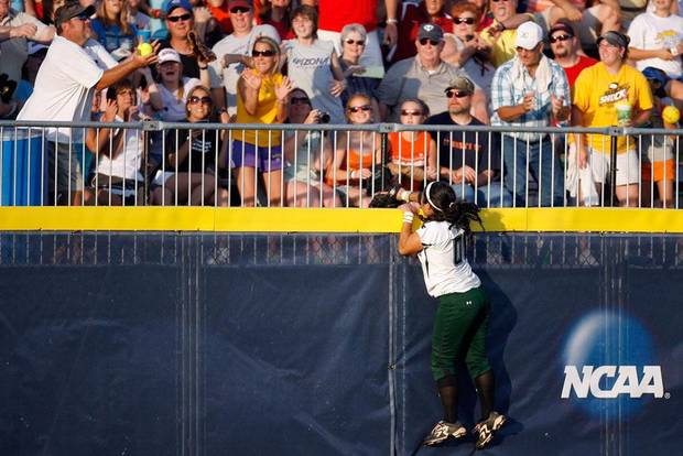 Hawaii's Kelly Majam climbs the fence as fans catch a UCLA home run ball during the Women's College World Series game between UCLA and Hawaii, Friday, June 4, 2010, in Oklahoma City. Photo by Sarah Phipps, The Oklahoman