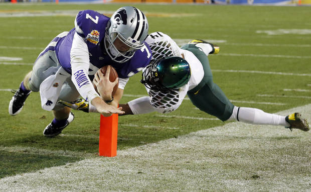 Kansas State quarterback Collin Klein (7) dives for a touchdown as Oregon cornerback Ifo Ekpre-Olomu (14) defends during the first half of the Fiesta Bowl NCAA college football game, Thursday, Jan. 3, 2013, in Glendale, Ariz. (AP Photo/Ross D. Franklin)