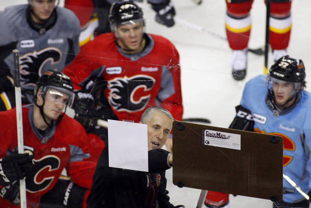Calgary Flames' head coach Bob Hartley, foreground center, marks out a drill as players, left to right, Curtis Glencross, Alex Tanguay and Paul Byron look on during training camp in Calgary, Alberta, Monday, Jan. 14, 2013. (AP Photo/The Canadian Press, Jeff McIntosh)