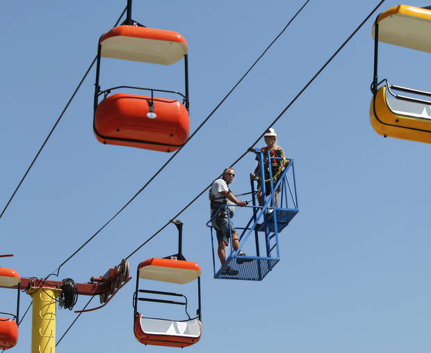 A carnival ride operator and an inspector from the Oklahoma Labor Department check the sky tram towers and cables. Setting up for Oklahoma State Fair on Thursday afternoon, Sep. 12, 2012. The 10-day event begins Thursday and ends Sunday, Sep. 23, 2012.   Photo by Jim Beckel, The Oklahoman