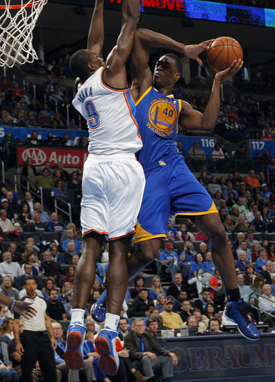 Oklahoma City 's Serge Ibaka (9) blocks a shot by Golden State's Harrison Barnes (40) during an NBA basketball game between the Oklahoma City Thunder and the Golden State Warriors at Chesapeake Energy Arena in Oklahoma City, Sunday, Nov. 18, 2012.  Photo by Garett Fisbeck, The Oklahoman