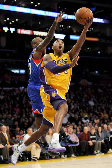 Los Angeles Lakers guard Kobe Bryant, right, shoots past Philadelphia 76ers guard Jason Richardson in the first half of an NBA basketball game, Tuesday, Jan. 1, 2013, in Los Angeles. (AP Photo/Gus Ruelas)