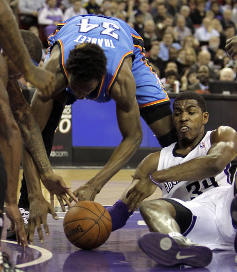 Oklahoma City Thunder center Hasheem Thabeet (34), of Tanzania, and Sacramento Kings forward Jason Thompson, right, scramble for the ball during the first quarter of  an NBA basketball game in Sacramento, Calif., Friday, Jan. 25, 2013. (AP Photo/Rich Pedroncelli) ORG XMIT: SCA105