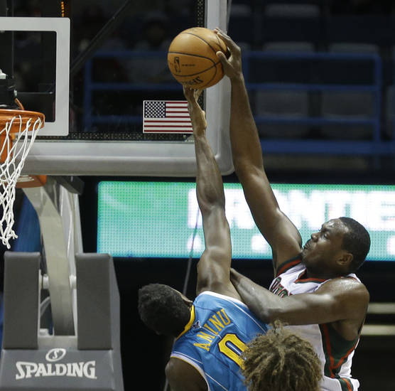 Milwaukee Bucks' Samuel Dalembert(21) has his shot blocked by New Orleans Hornets' Al-Farouq Aminu(0) during the first half of an NBA basketball game Saturday, Nov. 17, 2012, in Milwaukee. (AP Photo/Jeffrey Phelps)