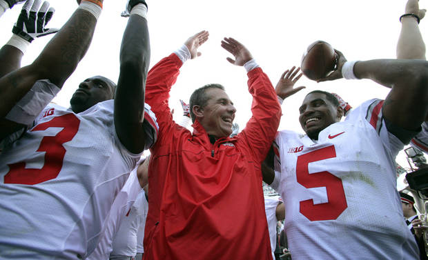 Ohio State coach Urban Meyer, center, celebrates with quarterback Braxton Miller (5) and defensive back Corey Brown (3) following a 17-16 win over Michigan State in an NCAA college football game, Saturday, Sept. 29, 2012, in East Lansing, Mich. (AP Photo/Al Goldis)