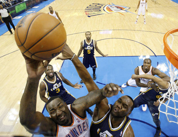 Oklahoma City Thunder center Kendrick Perkins, left, shoots in front of Utah Jazz center Al Jefferson, right, in the first quarter of an NBA basketball game in Oklahoma City, Friday, Nov. 30, 2012. Oklahoma City won 106-94. (AP Photo/Sue Ogrocki) ORG XMIT: OKSO108