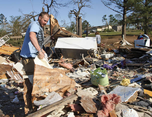 William Smith tugs at a piece of rubble as he helps clear out what is left of a friend's home in Tushka, Okla., Friday, April 15, 2011, following last night's tornado. (AP Photo/Sue Ogrocki)