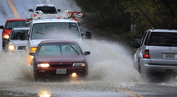 Cars are awash in floodwaters on Windsor Road at Pool Creek in Windsor, Calif., Friday Dec. 21, 2012 during a winter storm. (AP Photo/The Press Democrat, Kent Porter)
