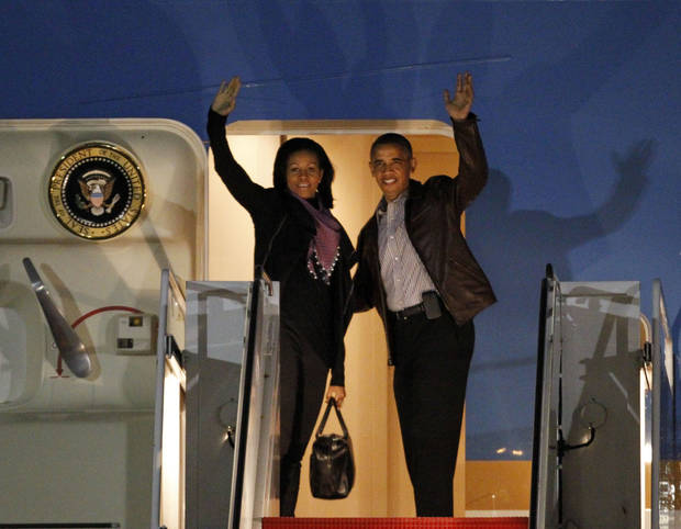 President Barack Obama and first lady Michelle Obama wave as they board Air Force One at Andrews Air Force Base, Md., Friday, Dec. 21, 2012 before departing for Hawaii. (AP Photo/Ann Heisenfelt)