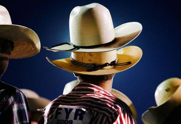 Cole Miller, Lahoma, Okla., wears a friend's hat while that cowboy competes in bull riding during an evening session of the International Finals Youth Rodeo at the Heart of Oklahoma Expo Center in Shawnee, Wednesday,  July 15, 2009.  Photo by Jim Beckel, The Oklahoman