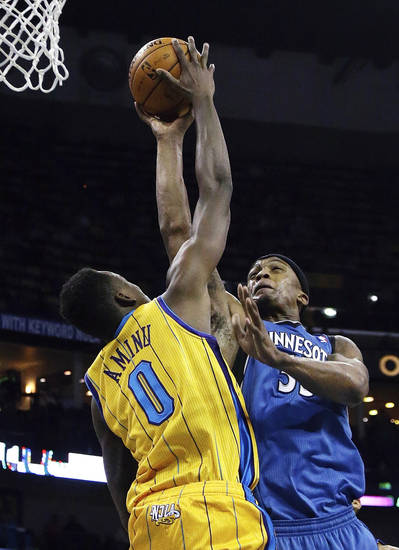 New Orleans Hornets forward Al-Farouq Aminu (0) blocks the shot of Minnesota Timberwolves forward Dante Cunningham (33) during the first half of an NBA basketball game in New Orleans, Friday, Jan. 11, 2013. (AP Photo/Bill Haber)
