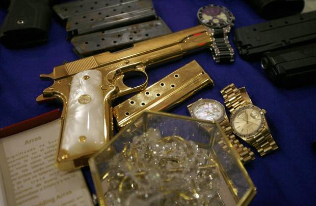 "A gold plated pistol and jewelry, allegedly seized from Manuel Alquisires Garcia, alias ""El Meme,"" sit on display during his presentation to the press of in Mexico City, Monday Sept. 12, 2011. According to the Navy, Alquisires Garcia escaped from prison in 2002, was detained in possession of several weapons on Sept. 10 and is a accused of belonging to the Gulf drug cartel. (AP Photo/Marco Ugarte) ORG XMIT: MXMU104"