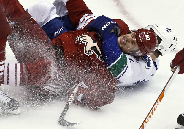Phoenix Coyotes' Antoine Vermette (50) gets taken down by Vancouver Canucks' Keith Ballard during the second period in an NHL hockey game, Thursday, March 21, 2013, in Glendale, Ariz. (AP Photo/Ross D. Franklin)