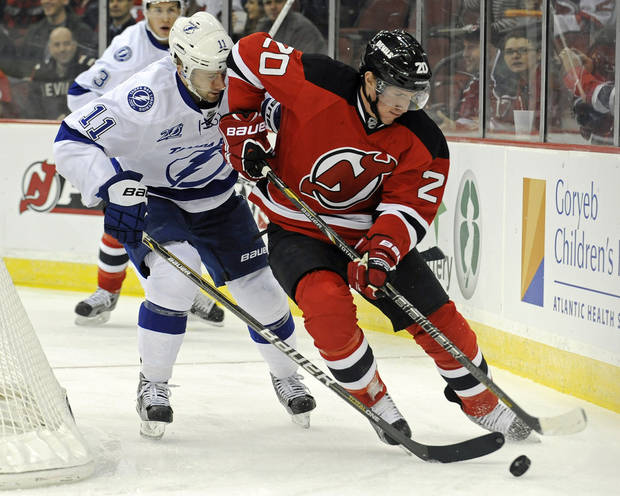 New Jersey Devils' Ryan Carter, right, handles the puck as he is checked  by Tampa Bay Lightning's Tom Pyatt during the first period of an NHL hockey game Tuesday, March 5, 2013, in Newark, N.J. (AP Photo/Bill Kostroun)