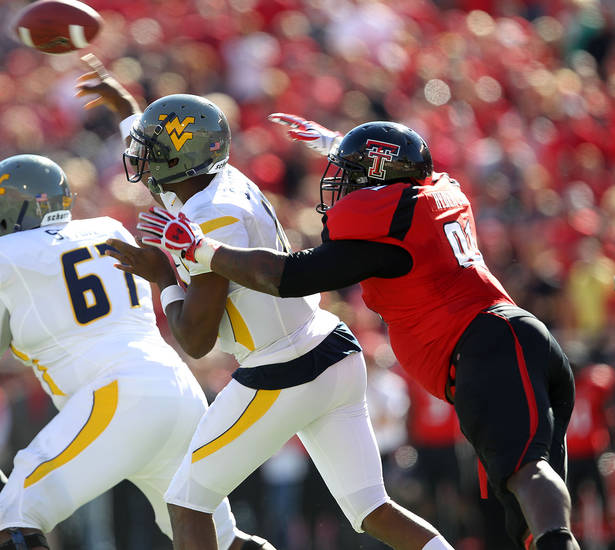 West Virginia's Geno Smith throws under pressure from Texas Tech's Kerry Hyder during an NCAA college football game in Lubbock, Texas, Saturday, Oct. 13, 2012. (AP Photo/Lubbock Avalanche-Journal, Stephen Spillman) LOCAL TV OUT