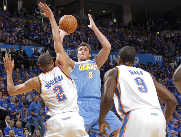 Denver's Danilo Gallinari (8) puts up a shot over Oklahoma City's Thabo Sefolosha (2) and Oklahoma City's Serge Ibaka (9) during the first round NBA playoff game between the Oklahoma City Thunder and the Denver Nuggets on Sunday, April 17, 2011, in Oklahoma City, Okla. Photo by Chris Landsberger, The Oklahoman