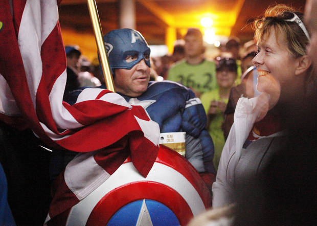 A runner dressed as Captain America takes shelter in a parking garage before the start the 14th Annual Oklahoma City Memorial Marathon in Oklahoma City, Sunday, April 27, 2014. The marathon was delayed over two hours beyond it's original start time of 6 a.m. Photo by KT King/The Oklahoman