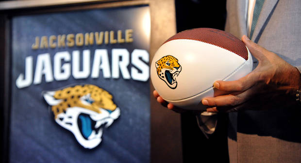 "Jacksonville Jaguars owner Shad Khan holds a football with the team's new logo, Tuesday, Feb. 5, 2013, in Jacksonville, Fla. The NFL football team unveiled a new logo and a ""Stand United"" theme for the 2013 season. (AP Photo/Florida Times-Union, Bruce Lipsky)"