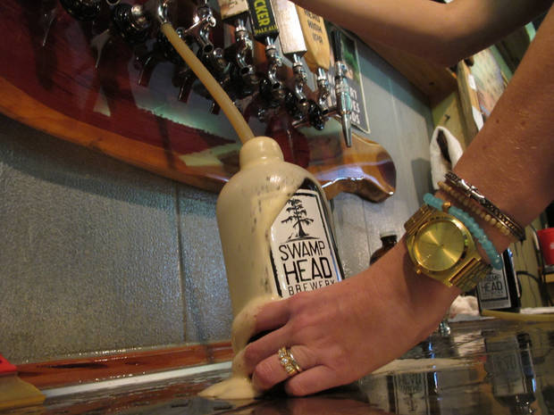 In this Friday, March 29, 2013 photo, a 32-ounce bottle, known among beer enthusiasts as a growler, is filled at the Swamp Head Brewery in Gainesville, Fla. Quart and gallon growlers are legal in Florida but half-gallon growlers are illegal. (AP Photo/Brendan Farrington)