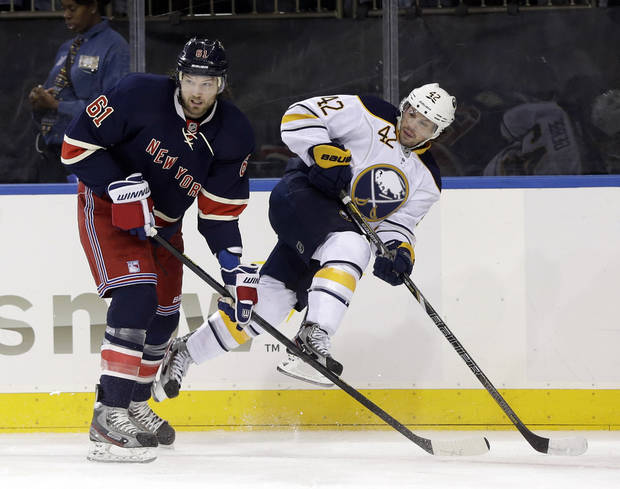 New York Rangers' Rick Nash (61) lifts Buffalo Sabres' Nathan Gerbe off the ice during the first period of their NHL hockey game in New York, Sunday, March 3, 2013. (AP Photo/Seth Wenig)