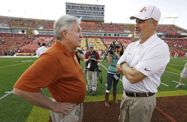Texas head coach Mack Brown, left, talks with Iowa State head coach Paul Rhoads before an NCAA college football game, Thursday, Oct. 3, 2013, in Ames, Iowa. (AP Photo/Charlie Neibergall)