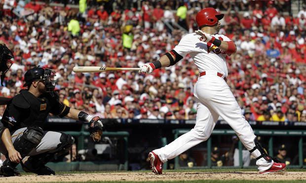 St. Louis Cardinals' Carlos Beltran hits a double against the Pittsburgh Pirates during the first inning in Game 2 of baseball's National League division series on Friday, Oct. 4, 2013, in St. Louis. Catching for the Pirates is Russell Martin. (AP Photo/Jeff Roberson)