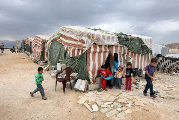 In this Tuesday, Oct. 2, 2012 photo, Syrian refugees children stand in front of their tents at a refugee camp in Arsal, a Sunni Muslim town eastern Lebanon near the Syrian border, has become a safe haven for war-weary Syrian rebels and hundreds of refugee families. Many in Arsal support the rebels, but the town�s stand is risking heightened tensions with its Shiite Muslim neighbors in an area controlled by Hezbollah, a militia that backs the Syrian regime. Deepening sectarian rifts are one of the ways in which Syria�s 18-month-old conflict is destabilizing an already volatile region. (AP Photo/Bilal Hussein)