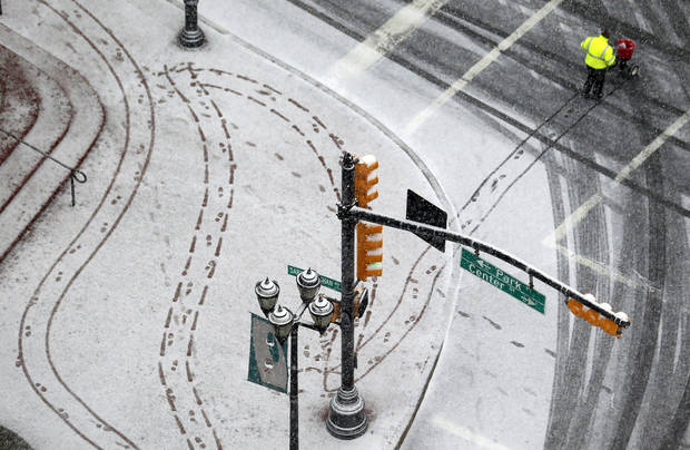 A person pushes a cart to spread salt on a snowy sidewalk at Military Park in downtown Newark, N.J. on Wednesday, Dec. 26, 2012. (AP Photo/Julio Cortez)