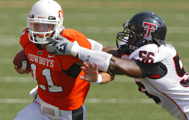 Oklahoma State quarterback Zac Robinson (11) tries to get past Texas Tech's Kellen Tillman (56) during the first half of the college football game between the Oklahoma State University Cowboys (OSU) and the Texas Tech University Red Raiders (TTU) at Boone Pickens Stadium  on Saturday, Sept. 22, 2007, in Stillwater, Okla. 