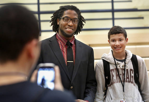 D. J. Ward, left, patiently filled requests from classmates to pose for pictures with him after he signed a letter of intent to play football at the University of Oklahoma.  More than a dozen Southmoore High School athletes signed letters of intent to play at various colleges and universities  during an afternoon signing ceremony  in the school's gymnasium on Wednesday, Feb. 6, 2013.  Photo by Jim Beckel, The Oklahoman