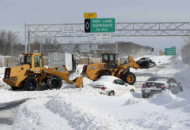 Payloaders clear snow from the Long Island Expressway just west of exit 59 Ocean Ave where several cars and a truck are abandoned after a snow storm on Saturday, Feb. 9, 31, 2013, in Ronkonkoma , N.Y. (AP Photo/Kathy Kmonicek) ORG XMIT: NYKK105