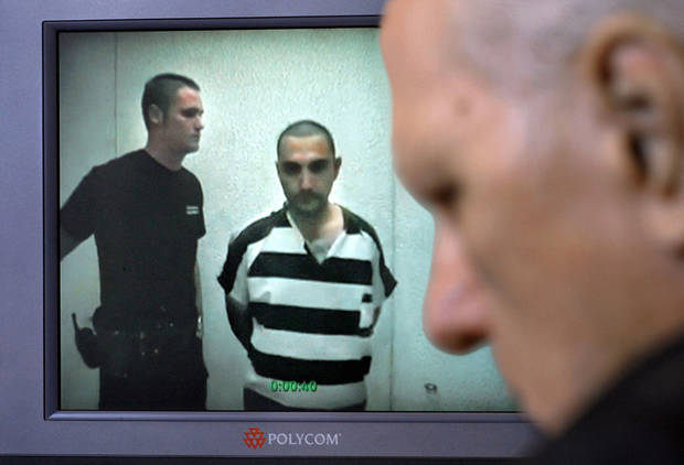 Murder suspect Luis E. Ruiz appeared before Special Judge Russell Hall, at right, during a video arraignment in Hall's chamber Tuesday, July 24, 2012.  Ruiz and partner Jimmy L. Massey face charges in the slaying of Carina Saunders in Bethany last fall.  Photo by Jim Beckel, The Oklahoman.