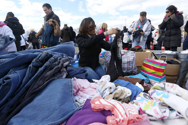Maria Heidelberg, center, sorts through donated clothing to be sent out to a neighborhood hit by Superstorm Sandy, Saturday, Nov. 3, 2012, in Staten Island, N.Y. (AP Photo/Julio Cortez) ORG XMIT: NYJC118