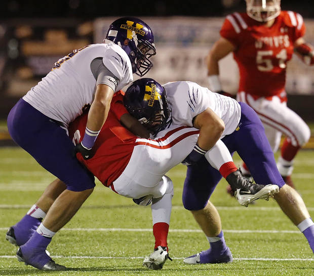 Davis' Dedrien Nowden is sandwiched between Vian tacklers Tre Locust, left, and Rowdy Simon. Vian Wolverines play Davis Wolves in the Class 2A semifinal game Friday night, Friday, Nov. 30, 2012, at Rose Field, Jim Darnell Stadium in Midwest City.  Photo by Jim Beckel, The Oklahoman