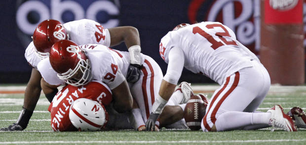 Oklahoma's Austin Box (12) recovers a fumble forced by Jeremy Beal (44) and Pryce Macon (94) on Nebraska's Taylor Martinez (3) during the Big 12 football championship game between the University of Oklahoma Sooners (OU) and the University of Nebraska Cornhuskers (NU) at Cowboys Stadium on Saturday, Dec. 4, 2010, in Arlington, Texas.  Photo by Chris Landsberger, The Oklahoman