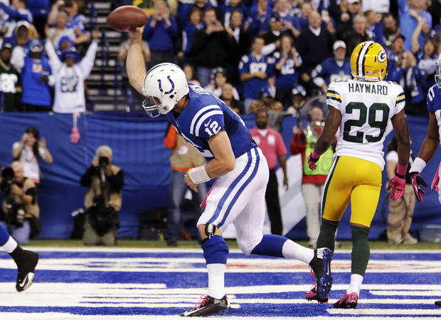 Indianapolis Colts quarterback Andrew Luck (12) celebrates his 3-yard touchdown run near Green Bay Packers cornerback Casey Hayward during the second half of an NFL football game in Indianapolis, Sunday, Oct. 7, 2012. (AP Photo/AJ Mast)