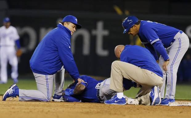 Toronto Blue Jays manager John Gibbons, left, and first base coach Dwayne Murphy, right, watch a trainer aid Jose Reyes during the sixth inning of a baseball game against the Kansas City Royals at Kauffman Stadium in Kansas City, Mo., Friday, April 12, 2013. (AP Photo/Orlin Wagner)