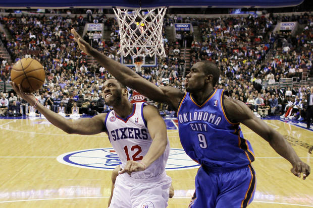 Philadelphia 76ers' Evan Turner, left, tries to get a shot past Oklahoma City Thunder's Serge Ibaka, of Congo, in overtime of an NBA basketball game, Saturday, Nov. 24, 2012, in Philadelphia. Oklahoma won 116-109. (AP Photo/Matt Slocum) ORG XMIT: PXC112