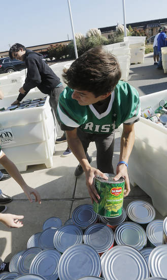 Matteo Hernandez helps load food collected for the Regional Food Bank of Oklahoma at Bishop McGuinness High School Friday, November 9, 2012.  The school collected 75,660 pounds of food. Photo by Doug Hoke, The Oklahoman