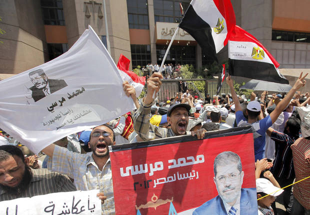 "Hundreds of Muslim Brotherhood supporters demonstrate outside the State Council in Cairo, Egypt, Tuesday, July 17, 2012, ahead of an anticipated Administrative Court ruling on the dissolution of Parliament. Arabic on the poster reads,""Mohammed Morsi for Egyptian presidency.""(AP Photo/Amr Nabil)"